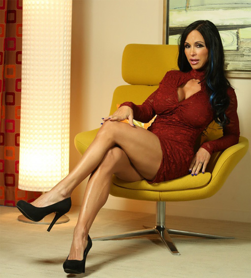 Jewels Jade seduta a gambe incrociate con lo sguardo da porcona